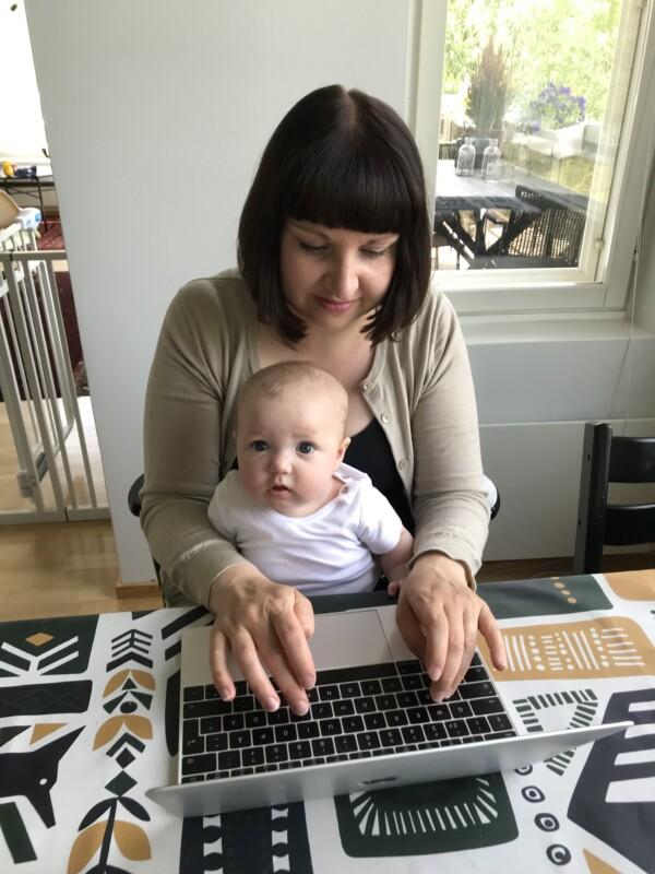 Vuoden 2021 kuntavaaliehdokas (Kokoomus) Anniina Iskanius tekee etätöitä läppärillä lapsi sylissään.